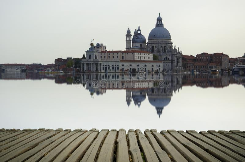 Fine art image with Grand Canal and Basilica Santa Maria della Salute, reflected on the water surface,. With wood planks floor for foreground, Venice, Italy royalty free stock photo