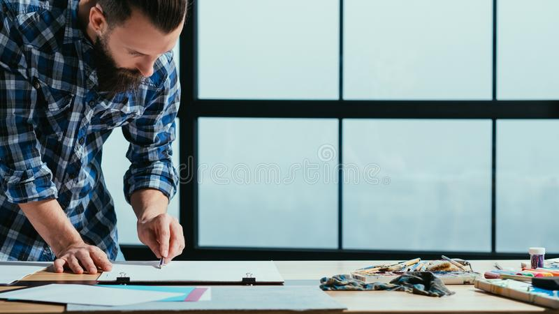Fine art master class drawing lefthanded painter. Fine art master class. Young talented lefthanded male painter drawing with graphite pencil on sketch board royalty free stock photography