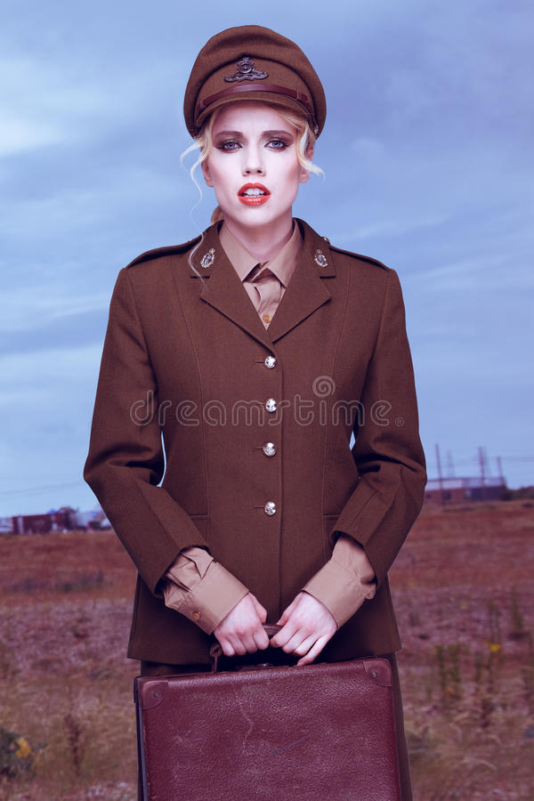Fine art portrait of an army officer in the field. Fine art portrait of a gorgeous young blond female army officer in a stylish uniform holding a small vintage royalty free stock photo