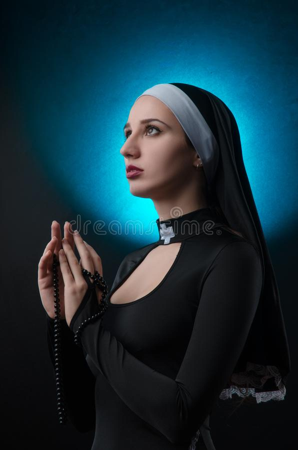 Fine art portrait of a novice nun in deep prayer with rosary stock photography