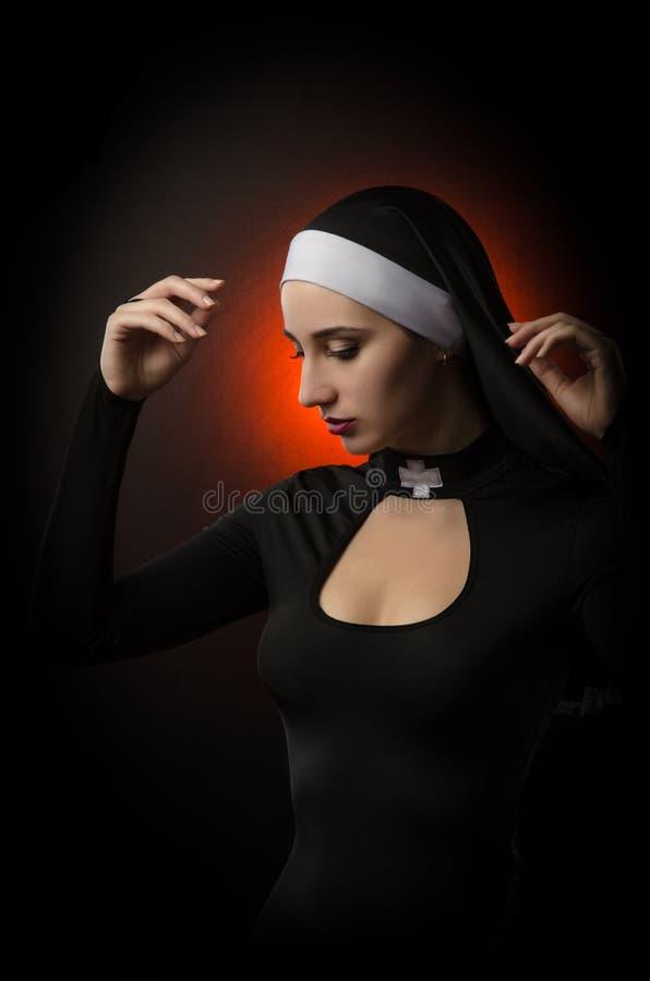 Fine art portrait of a novice nun in deep prayer with rosary stock image