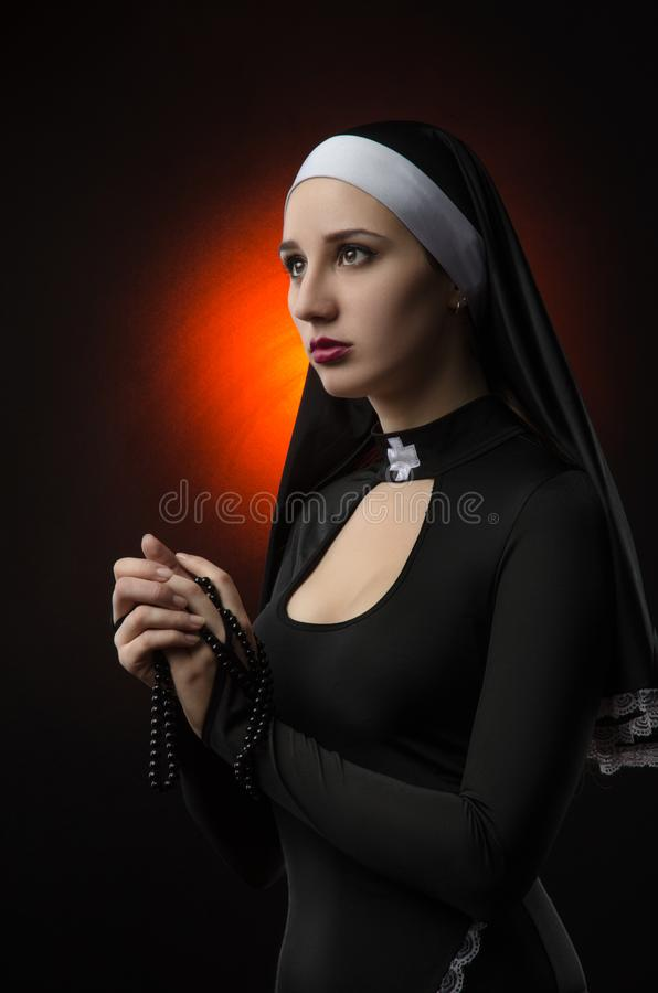 Fine art portrait of a novice nun in deep prayer with rosary royalty free stock images