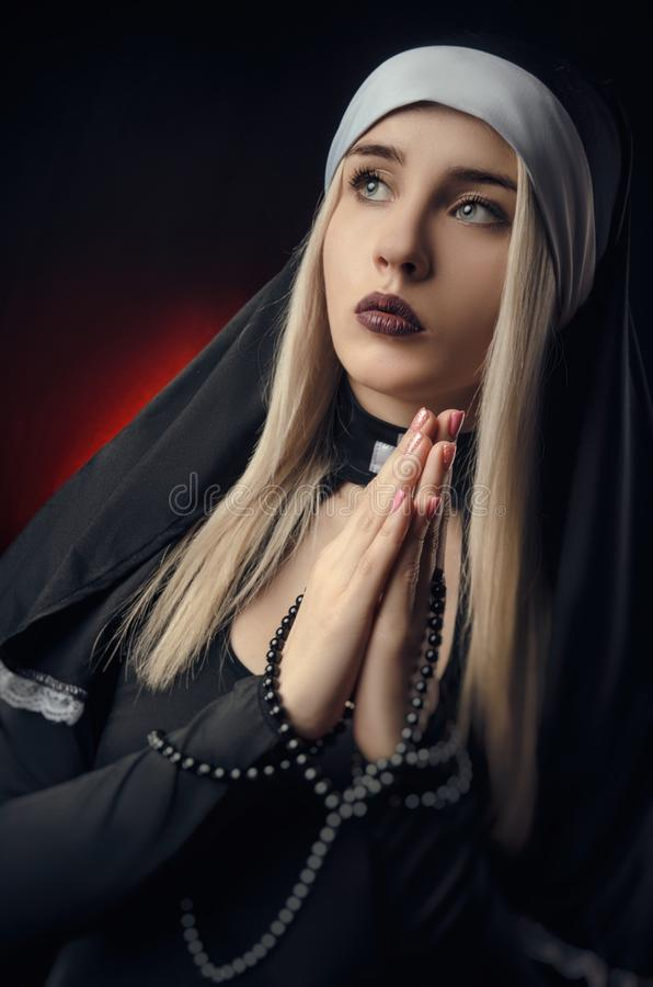 Fine art portrait of a novice nun in deep prayer with rosary royalty free stock photos