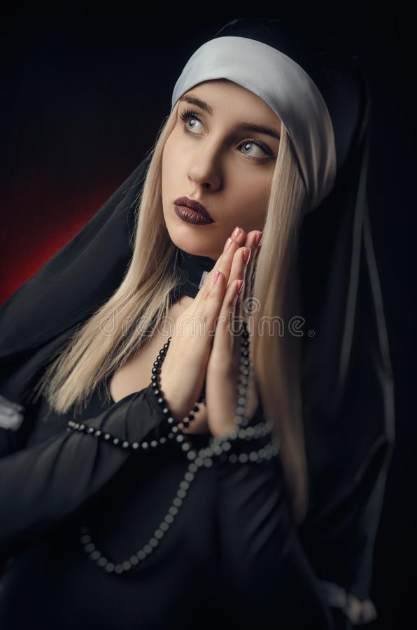 Fine art portrait of a novice nun in deep prayer with rosary stock images