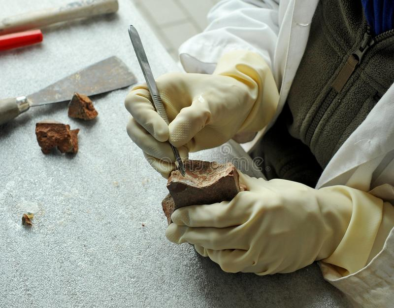 A fine arts restorer cleaning the antique ceramic with scalpel royalty free stock image