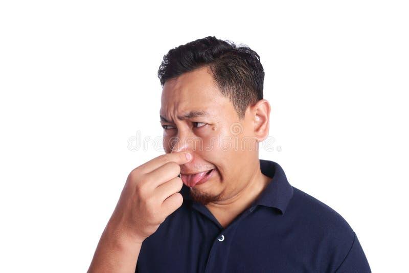 Fine asiatica dell'uomo il suo malato del naso di cattivo odore fotografia stock