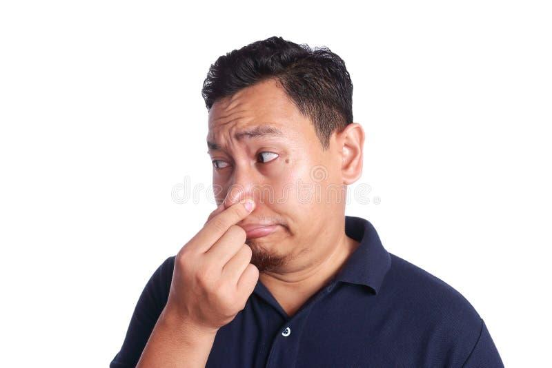 Fine asiatica dell'uomo il suo malato del naso di cattivo odore immagini stock