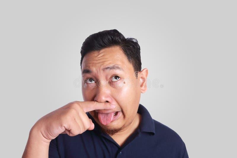 Fine asiatica dell'uomo il suo malato del naso di cattivo odore immagini stock libere da diritti