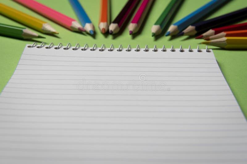 Fine in bianco del taccuino su con le matite colorate nel fondo immagini stock libere da diritti
