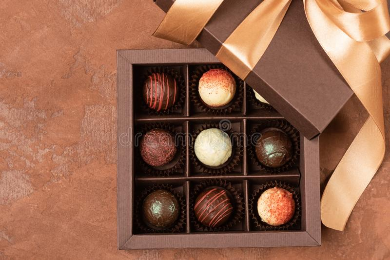 Fine chocolates in craft box with satin ribbon on a dark background. Flat layout. Festive concept. Copy space. Fine chocolates in craft box with satin ribbon on stock photography