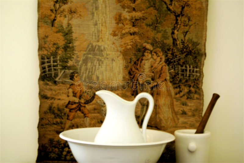 Fine collectibles. In interior design with tapestry,wash basin and pitcher,mortar,pestle royalty free stock photo