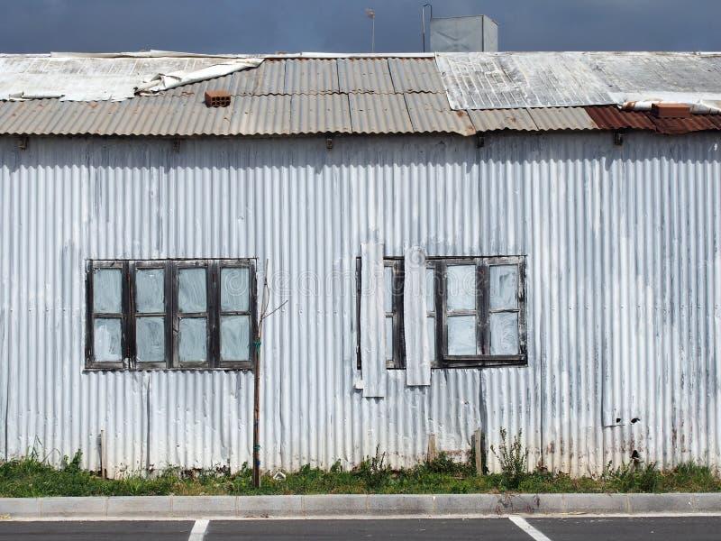 fine completa della struttura su di vecchia costruzione dilapidata misera del ferro ondulato con con chiuso dipinto sopra le fine immagine stock libera da diritti