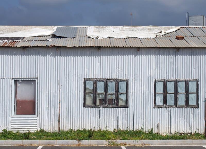 fine completa della struttura su di vecchia costruzione dilapidata misera del ferro ondulato con con chiuso dipinto sopra le fine fotografia stock