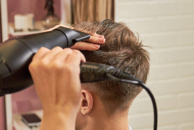 Fine dei capelli di secchezza del barbiere su fotografia stock libera da diritti