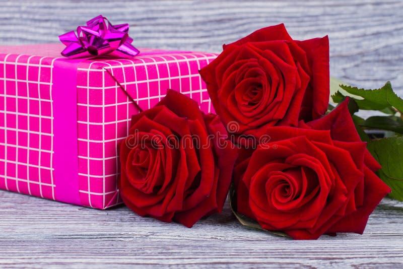 Fine del contenitore di regalo e delle rose rosse su fotografia stock libera da diritti