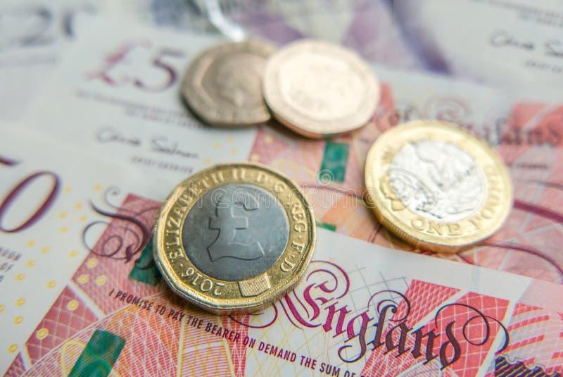 Fine del fondo finanziario delle banconote e delle monete della libbra britannica su fotografie stock