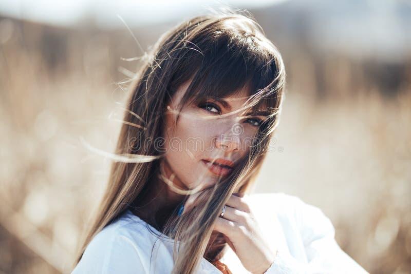Fine del ritratto su di giovane bella donna, sulla natura vaga molla ragazza bionda con lo sguardo sexy e la camicia bianca, sole immagini stock
