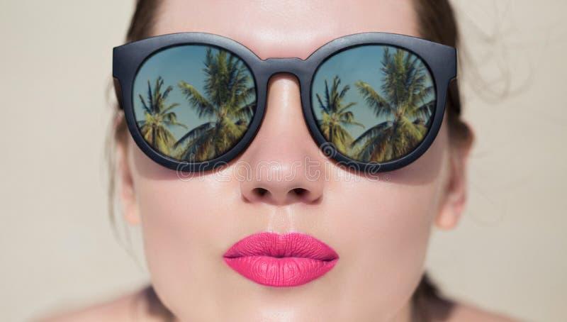 Fine del ritratto su di una donna graziosa con gli occhiali da sole immagini stock libere da diritti