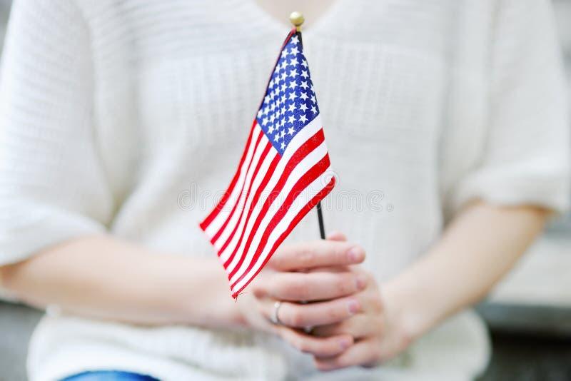 Fine della bandiera americana della tenuta della giovane donna su immagine stock