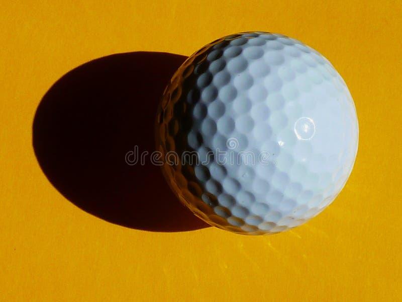 Fine della palla da golf su su fondo giallo con forte ombra fotografia stock libera da diritti