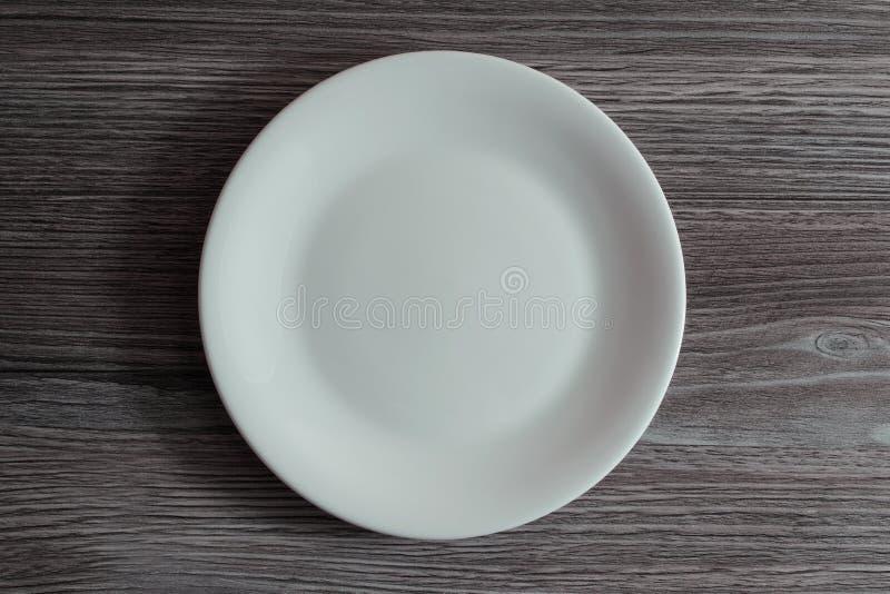 Fine di cui sopra diretta di spese generali della cima sulla foto di vista di un piatto rotondo ceramico bianco vuoto su fondo di immagini stock libere da diritti
