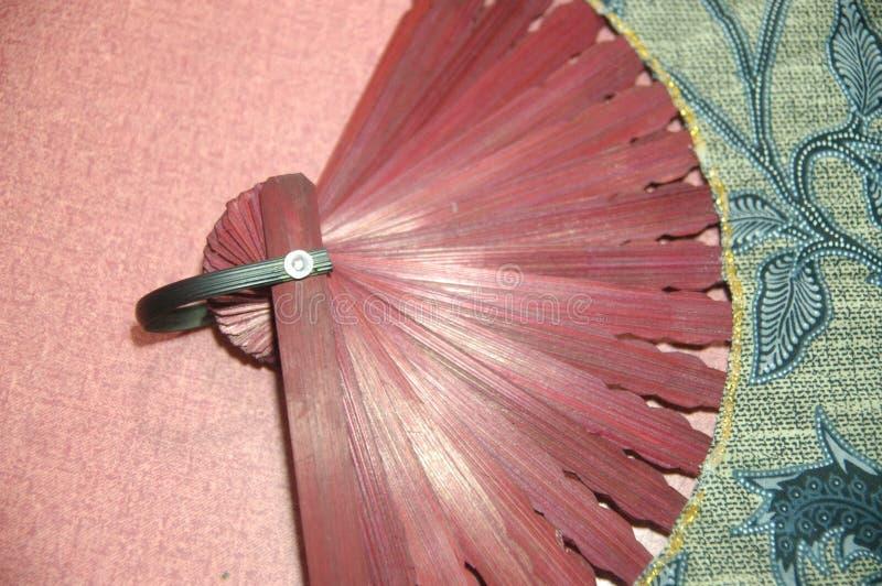 Fine di legno di colore rosso del ventaglio della donna su fotografia stock libera da diritti