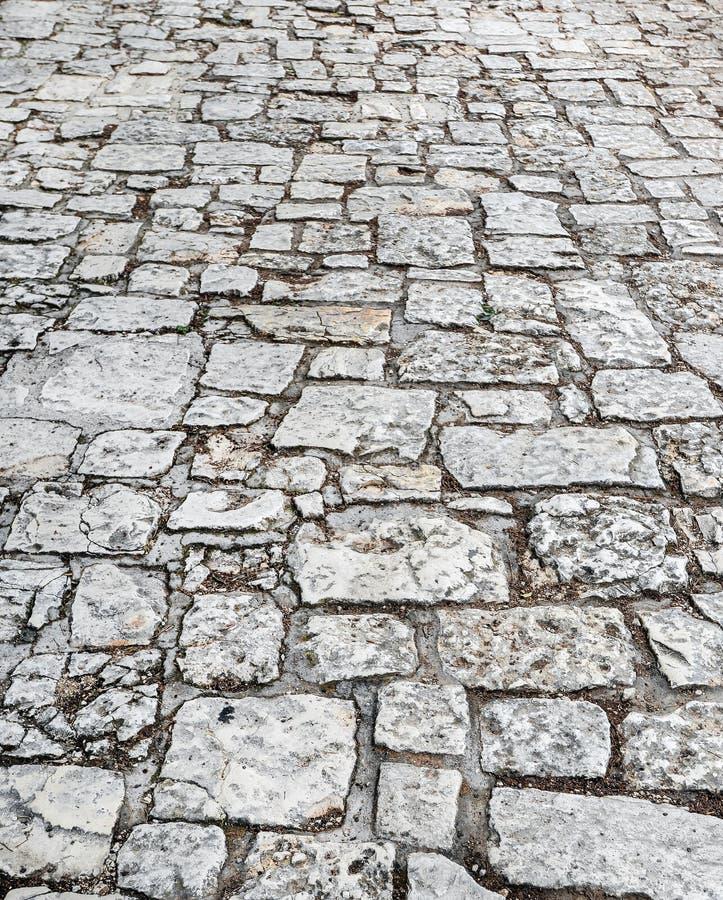 Fine di pietra della strada su Vecchia pavimentazione di granito Marciapiede grigio del ciottolo Struttura alta o d'annata di der fotografie stock