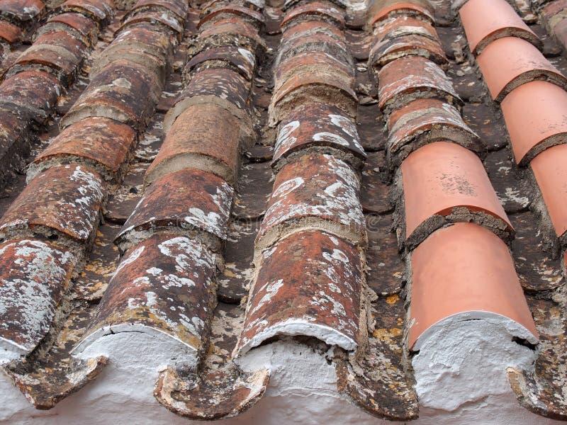 fine di prospettiva su di vecchie mattonelle di tetto riparate rosse di terracotta con danno e struttura fotografia stock