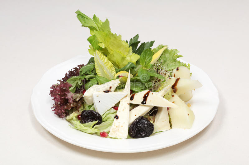 Fine dining meal, rucola salad. Rucola salad with juicy melon, dried plums and brie cheese bathed in the delicate dressing of balsamic vinegar and honey and royalty free stock photography