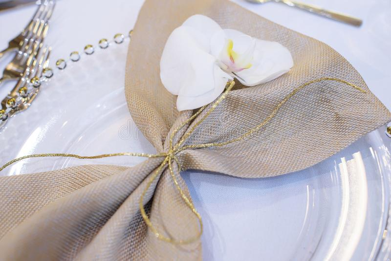 Fine dining table setting featuring transparent plates, beige linen napkin with natural orchid with golden decorations royalty free stock image