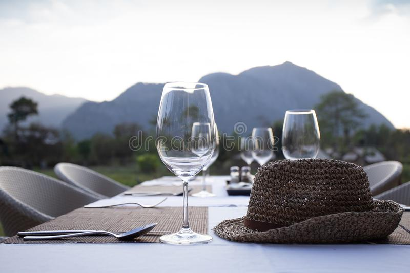 A fine dinner table set with high wine glass and utensils with a weave hat on the table with mountain view. A fine dinner table set with empty high wine glass stock photos