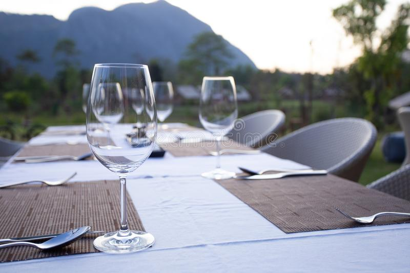 A fine dinner table set with high wine glass and utensils on the table with mountain view. A fine dinner table set with empty high wine glass and utensils on stock image