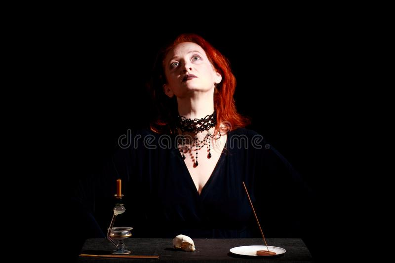 Fine emotional redhead witch with magical decorations and live expressions. Table with bird skull, candles and lamp. Black wizard background stock image