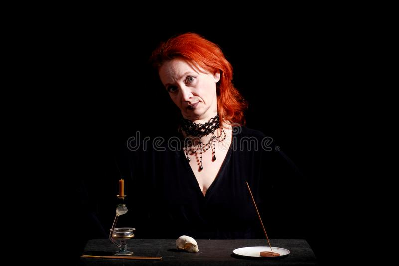 Fine emotional redhead witch with magical decorations and live expressions. Table with bird skull, candles and lamp. Black wizard background royalty free stock image