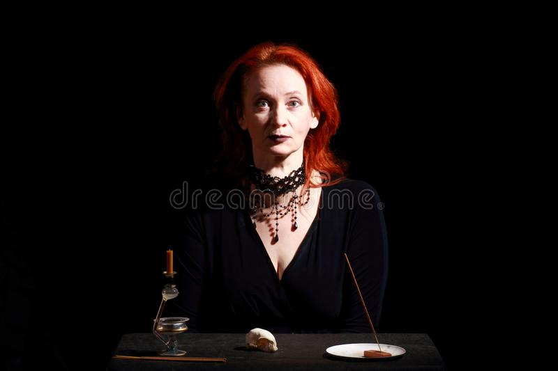 Fine emotional redhead witch with magical decorations and live expressions. Table with bird skull, candles and lamp. Black wizard background stock images