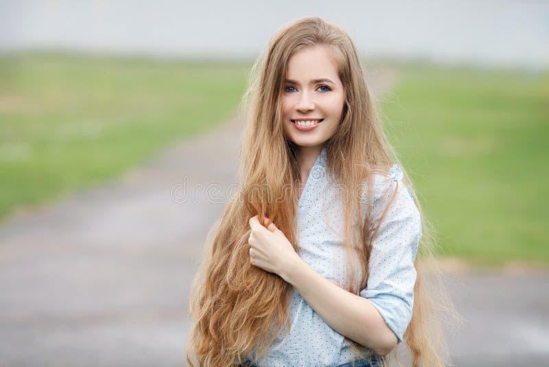 Fine emozionale sul ritratto di una donna bionda graziosa adulta con capelli extra-lunghi splendidi che posano all'aperto contro  fotografie stock