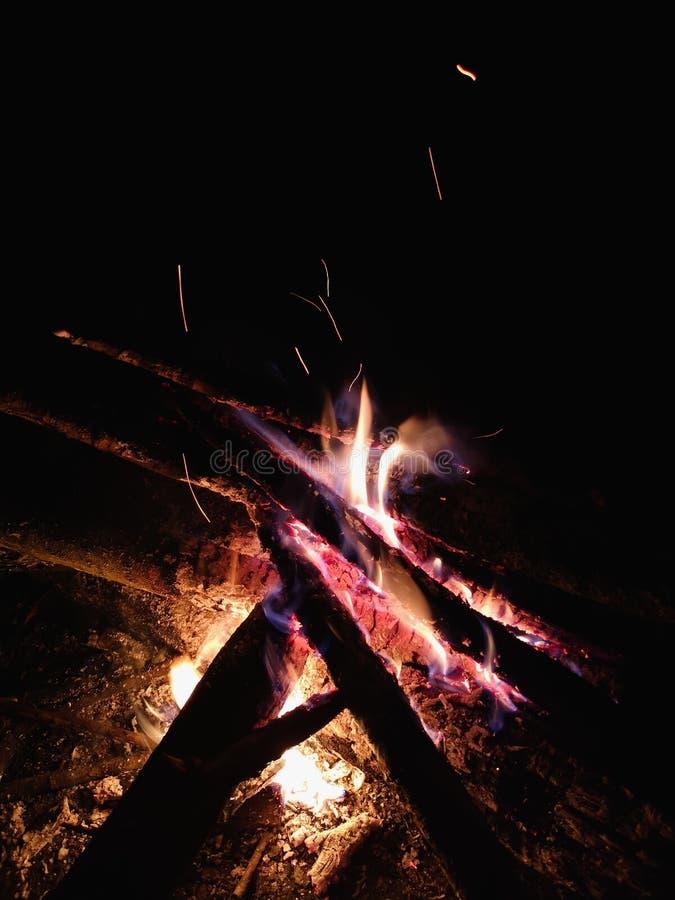 Fine estrema su delle scintille del fuoco che si muovono sul cielo notturno scuro come fondo nero che viene brillantemente dalla  fotografia stock libera da diritti