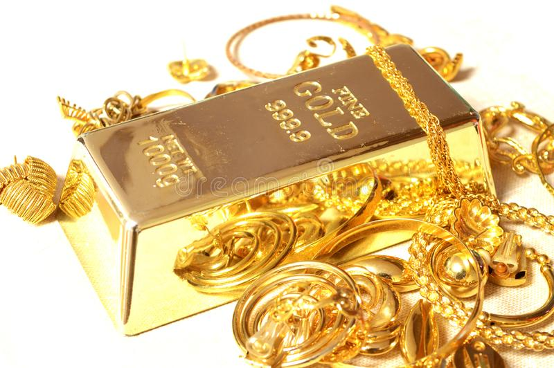 Gold Bar and Jewelry. A fine Gold Bar surrounded by compliamenting jewelry stock image