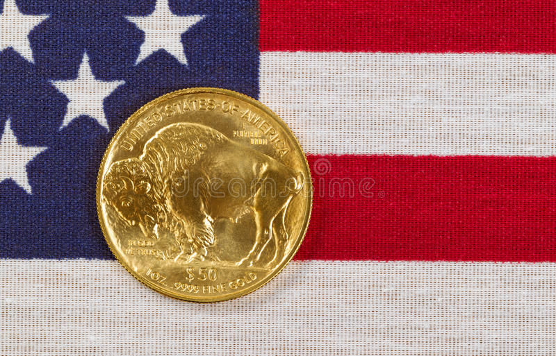 Fine gold Buffalo Coin on USA flag background. United States Mint issued American Buffalo coin, fine gold, on USA flag royalty free stock photography