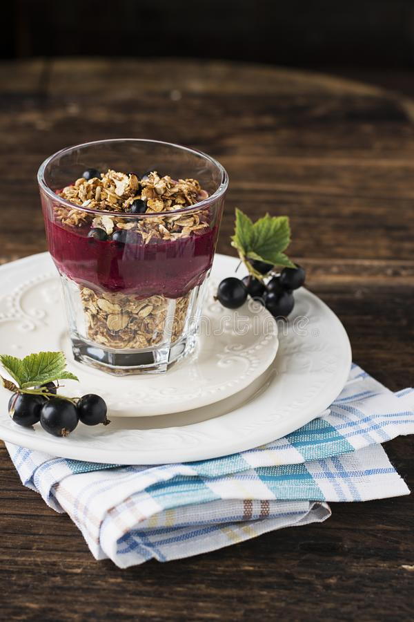 A fine homemade breakfast of granola and berry currant puree from fresh garden organic berries in a simple glass serving stock photo