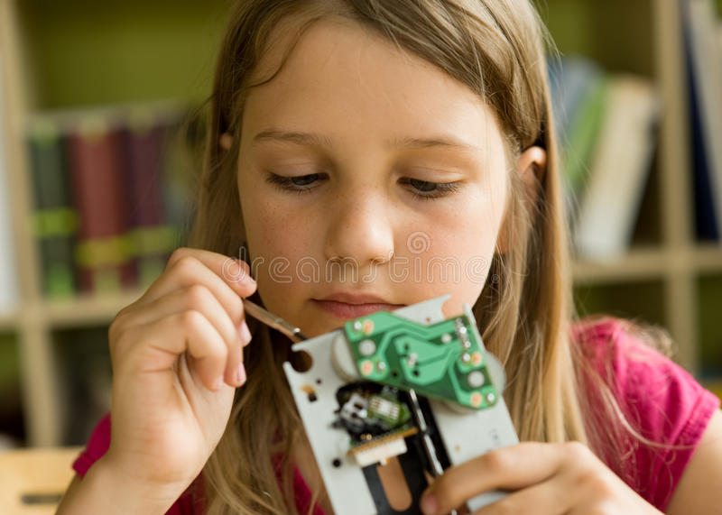 Fine motor skills. School girl busy with tools and mechanism stock images