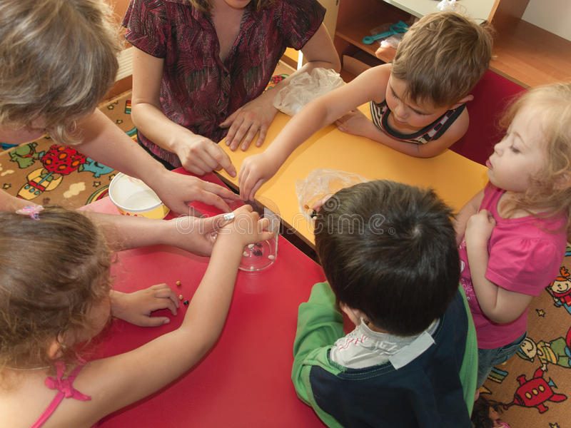 Fine motor skills. A group of children develop fine motor skills using beans stock images