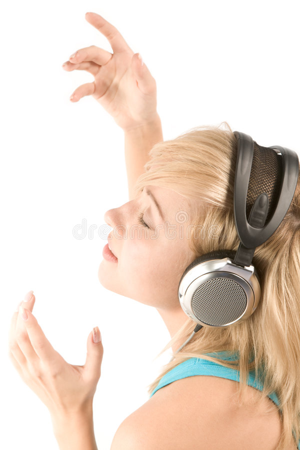 Fine rhythm. Photo of young female in headphones inspired by modern music with her arms raised stock photo