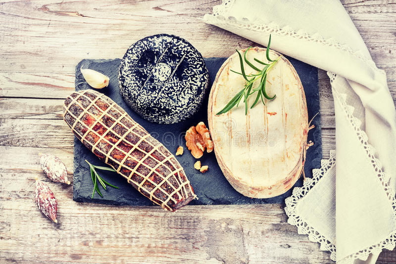 Fine selection of French cheese and sausages on stone plate. Foo. Fine selection of French cheese and sausages on stone plate. Gourmet dinner concept with copy stock photography