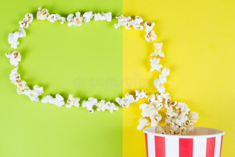 Fine sopraelevata di alto angolo di cui sopra superiore sulla foto di vista di popcorn con la borsa a strisce colta e bianca che  immagine stock
