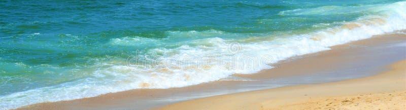 Fine sopraelevata su su un'ondata di bolle della schiuma del mare sulla sabbia bagnata della spiaggia, in una zona di marea dell' fotografia stock