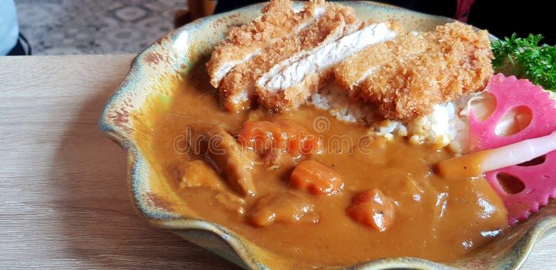 Fine su curry giapponese piccante caldo con carne di maiale e riso fritti in piatto sulla tavola di legno fotografie stock libere da diritti