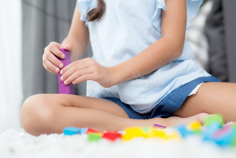 Fine su del bambino della mano che gioca con il blocco di plastica variopinto al pavimento immagine stock