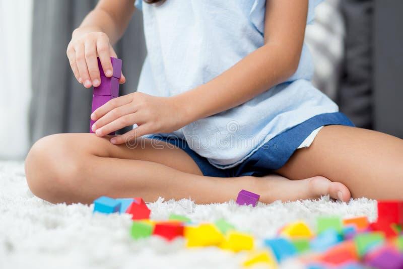Fine su del bambino della mano che gioca con il blocco di plastica variopinto al pavimento fotografia stock libera da diritti