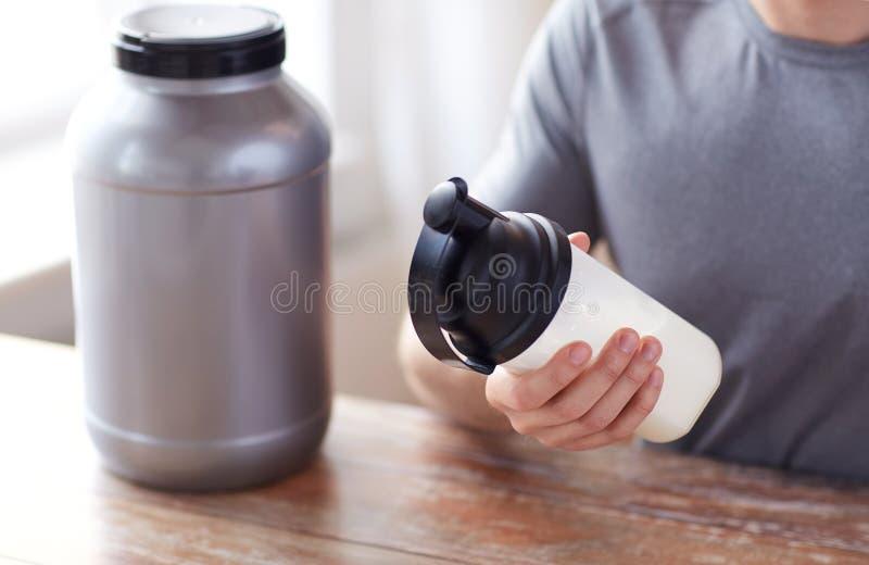 Fine su dell'uomo con la bottiglia ed il barattolo di scossa della proteina fotografia stock